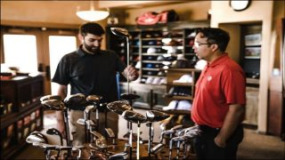 Golf Player Looking at Clubs in a Shop