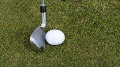 An image of a golf club next to a golf ball