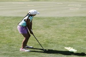 A girl golfer hitting a shot on the golf course