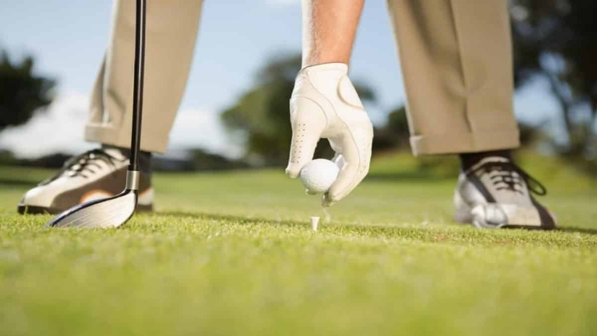 Golfer Placing Golf Ball on Golf Course