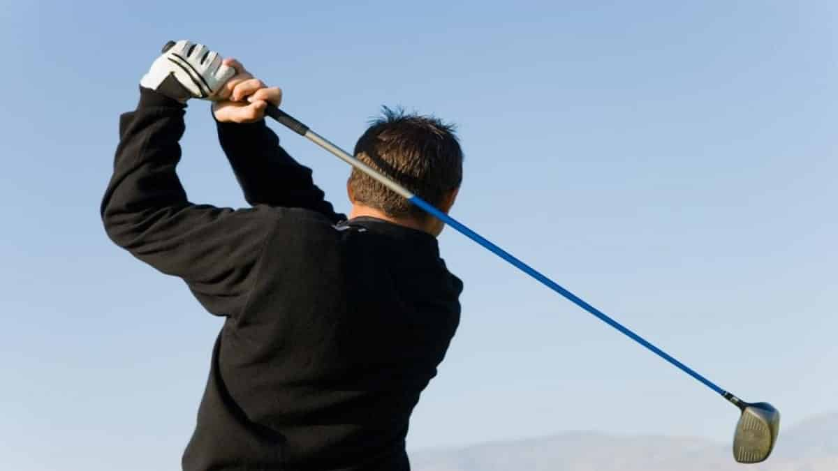 Golfer using an iron club to hit the ball