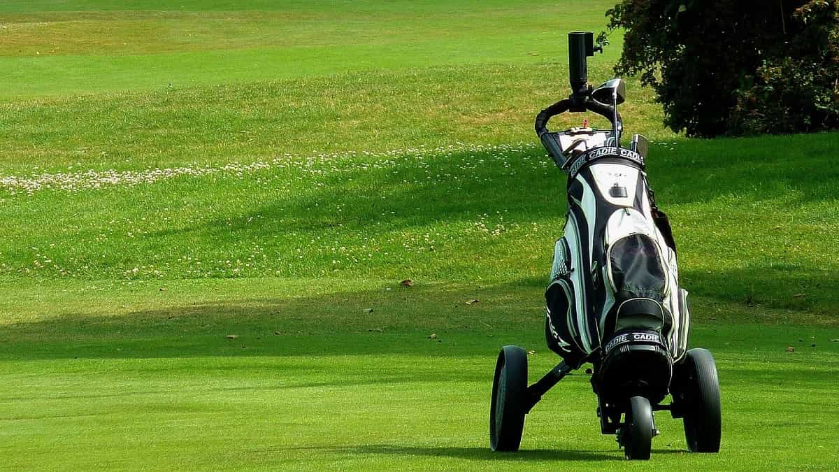 A golf bag with a trolley stand on the golf course
