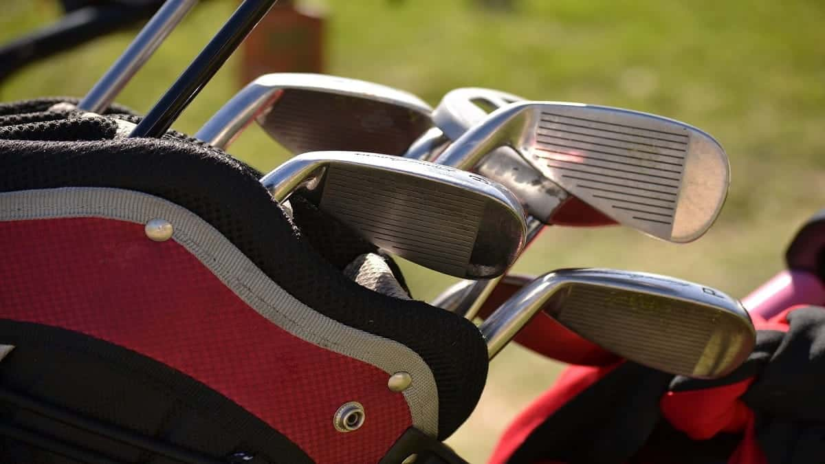 Golf clubs in bag on a golf field.
