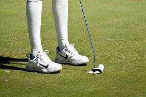 Golfer wearing spikeless shoes