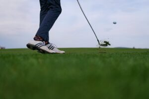 A golfer mid-swing with the golf ball in the air.