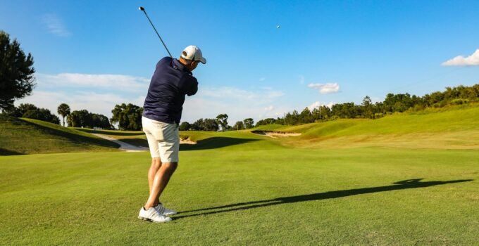 A golfer mid-swing and his golf ball in the air.